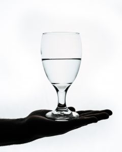 wine glass with water balanced on palm of hand